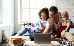 header-couple-with-baby-looking-at-laptop